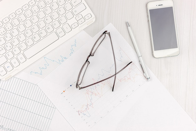 Flat lay photo of white office desk with laptop, smartphone, eyeglasses, notebook and pen with copy space background. mockup