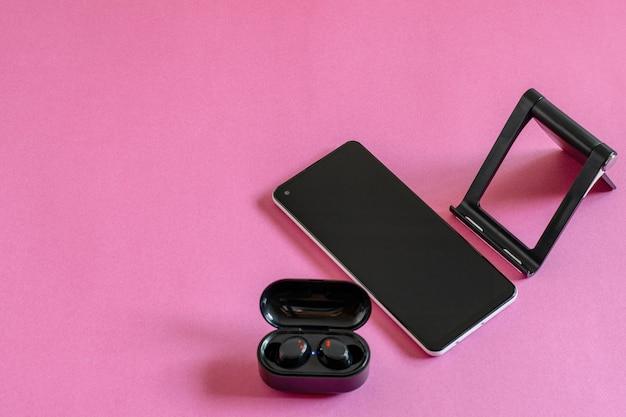 ピンクの背景に携帯電話、ワイヤレスイヤホン、電話スタンドを備えたフラットレイ写真。現代の技術の概念。