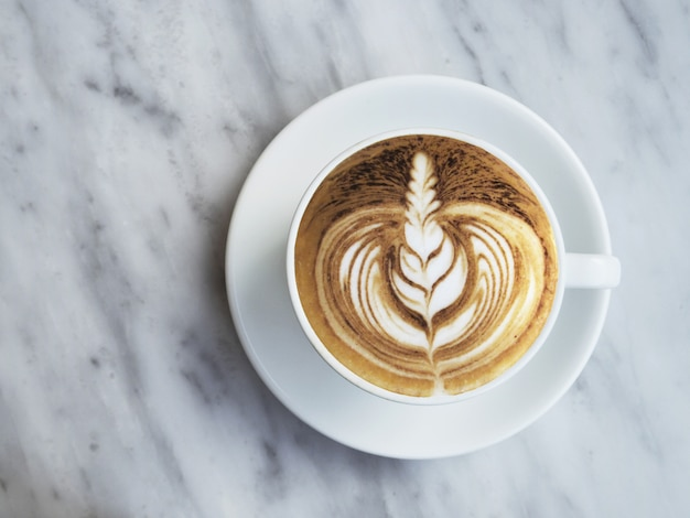 Flat lay photography of coffee with beautiful latte art on white marble background.