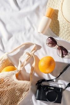 フラットレイピクニック、メガネ、オレンジバッグ、日焼け止めクリーム、スペースのある麦わら帽子。夏の気分