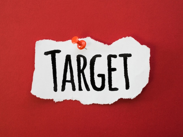 Flat lay of piece of paper with target and pin