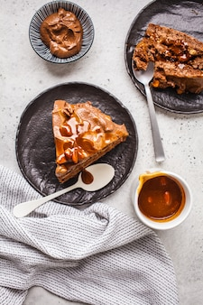 Flat lay of pieces of homemade snickers cake with chocolate cream and caramel on a black saucer, white background.