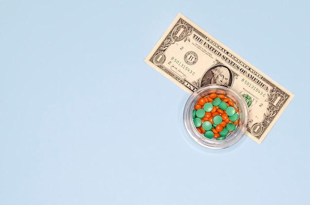 Плоские лежал таблетки и деньги на синем с копией пространства. стоимость лекарств. концепция здравоохранения, платной медицины, коррупции.