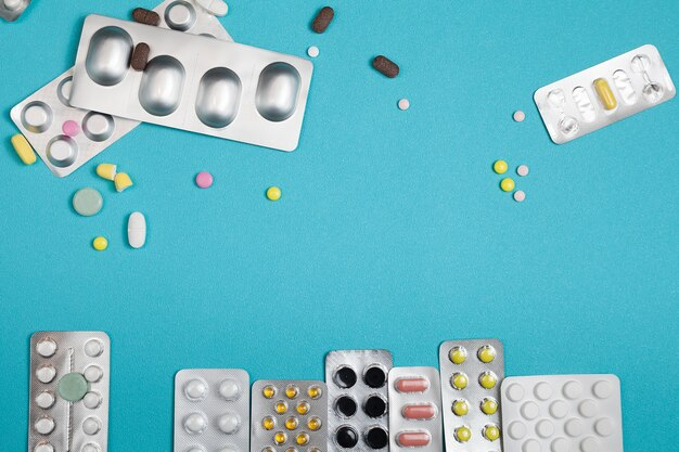 Flat lay of pills on blue with copy space, medical and healthcare concept.