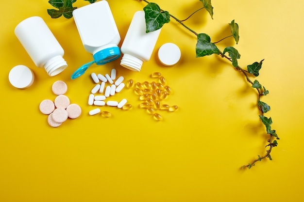 Flat lay of pills, fish oil, vitamins with green leavws on yellow background, healthcare concept, healthy food, supplements for healthy good life, immune booster.