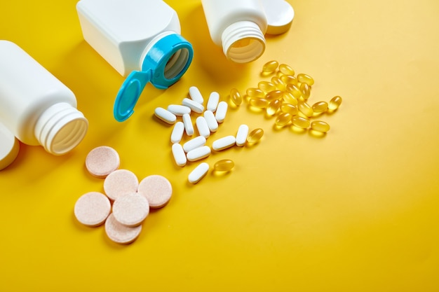 Flat lay of pills, fish oil, vitamins with green leavws on yellow surface