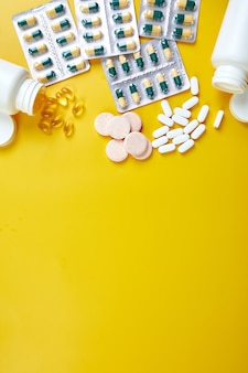 Flat lay of pills, fish oil, vitamins on yellow surface
