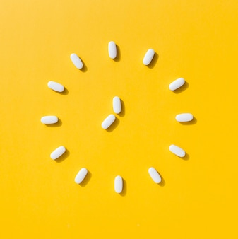 Flat lay of pills making clock shape