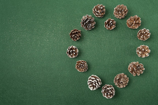 Flat lay of pinecone christmas decorations on a green surface