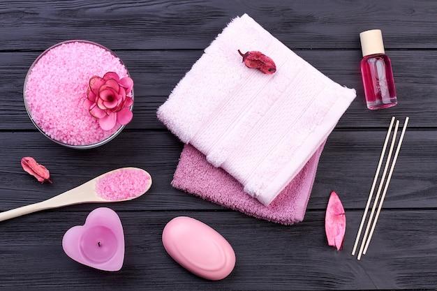 어두운 나무에 평평한 누워 분홍색 목욕 바디 케어 액세서리. 수건과 비누로 소금.