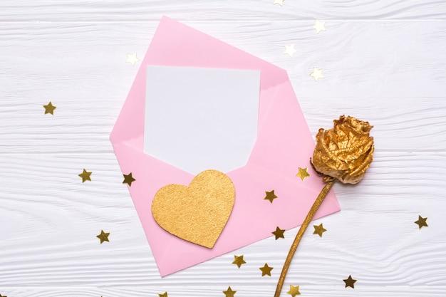 Плоский розовый конверт с запиской, золотой розой и золотым сердцем на белом деревянном фоне