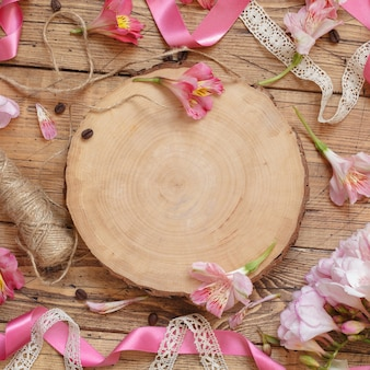 Flat lay of pink flowers and wooden board with copy space on wooden table. beautiful peruvian lilies layout with space for template. romantic holiday celebration concept