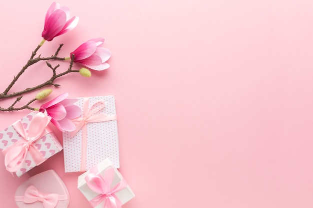Flat lay of pink gifts with magnolia and copy space