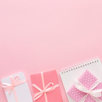 Flat lay of pink gifts with notebook and copy space