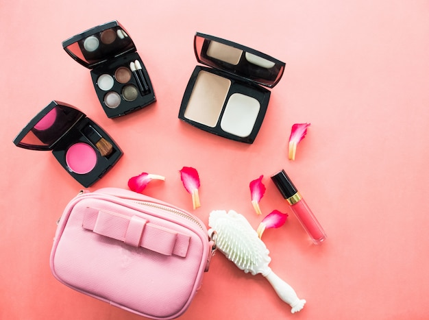 Flat lay of : pink handbag with cosmetic accessories.