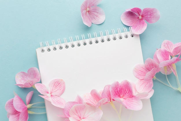 Flat lay pink hydrangea on blank notebook
