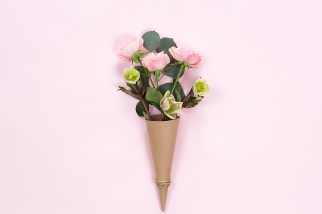Flat lay of pink rose flowers in a eco paper cornet isolated
