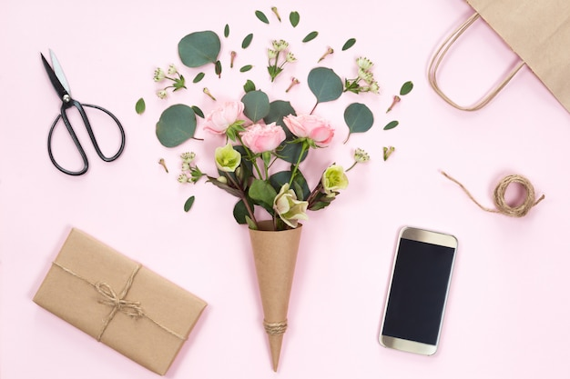 Flat lay of pink rose flowers in a eco paper cornet