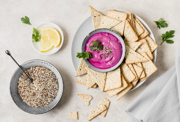 Flat lay of pink sauce with crackers and lemon