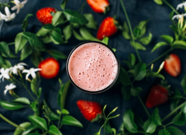 Flat lay pink smoothie next to strawberries and leaves