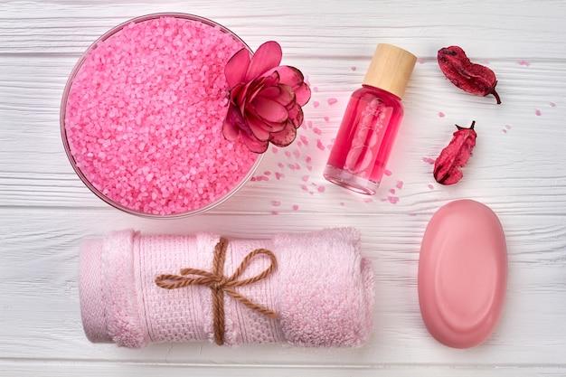 흰색 나무 책상에 평평한 분홍색 스파 액세서리. 비누와 소금이 묻은 수건.