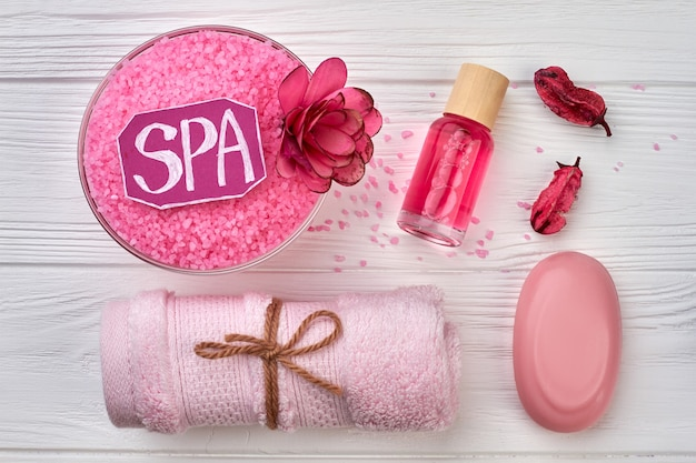 Flat lay pink spa accessories on white wooden desk