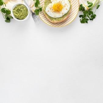 Плоский лаваш с авокадо и жареным яйцом на тарелке с копией пространства