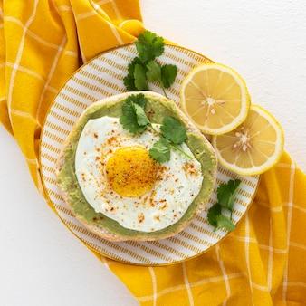 Плоская лаваш с авокадо и жареным яйцом на тарелке