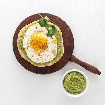 Flat lay pita with avocado spread and fried egg on cutting board