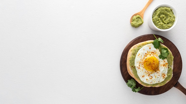 Flat lay pita with avocado spread and fried egg with copy-space