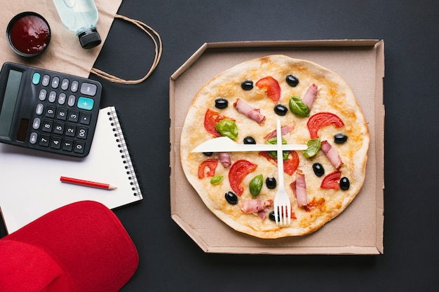 Flat lay pizza in a box with calculator