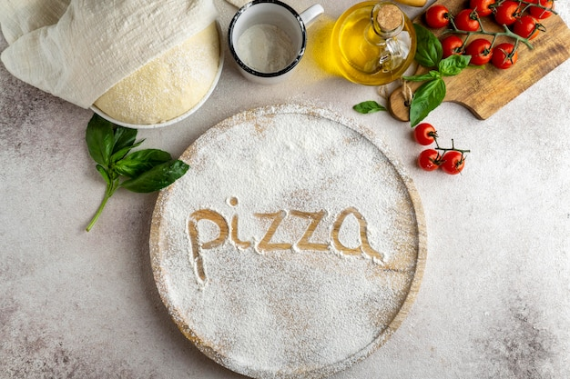 Flat lay of pizza dough with wooden board and word written in flour