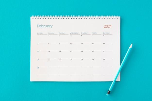 青い背景の上のフラットレイプランナーカレンダー
