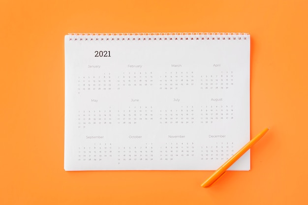 Flat lay planner calendar on orange background