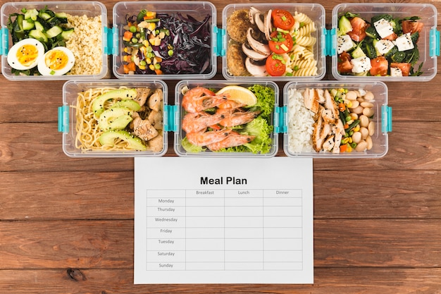 Flat lay of plastic casseroles with food and meal plan