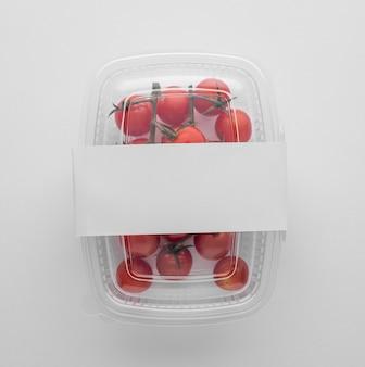 Lay piatto di imballaggi in plastica con pomodori