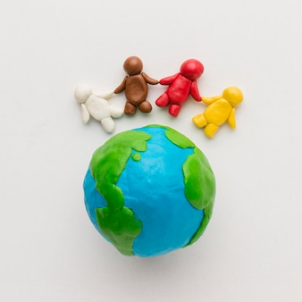 Flat lay of plasticine globe and people