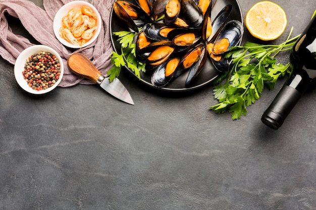 Flat-lay plate of cooked mussels and wine with copyspace