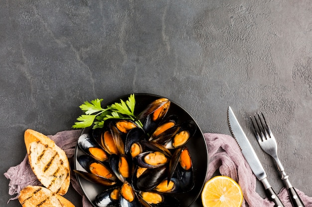 Flat-lay plate of cooked mussels with copy space