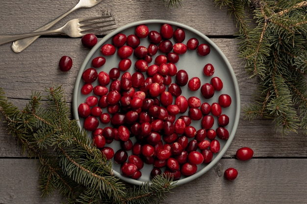 Flat lay of plate of cranberries with pine and forks