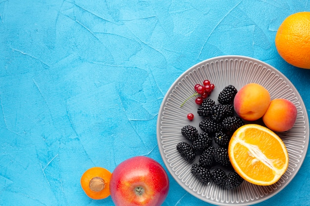 Flat-lay plate of fresh berries and fruits with copyspace