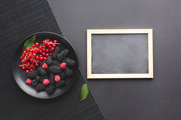Flat-lay plate of fresh berries with blackboard