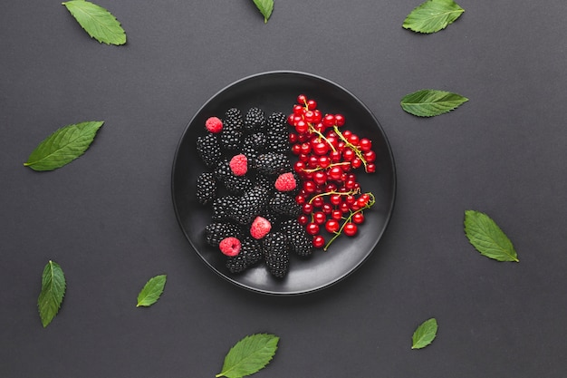Flat-lay plate of fresh berries with leaves