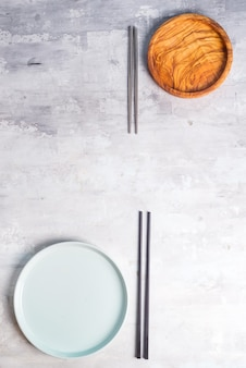 Flat lay of plate and iron sticks on grey . empty plate. ,food, zero waste .