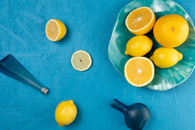 Flat lay of plate of lemons on blue background