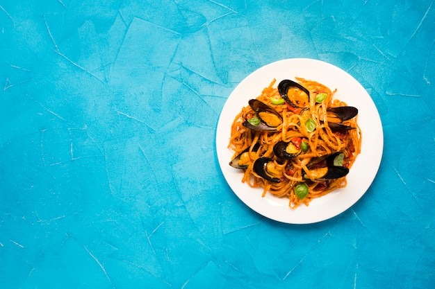Flat-lay plate of mussel pasta with copyspace