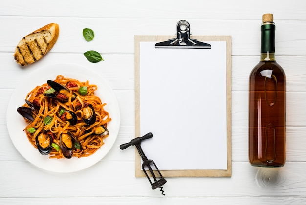 Flat-lay plate of mussels pasta and wine with clipboard