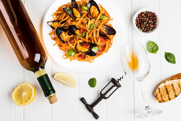 Flat-lay plate of mussels pasta and wine