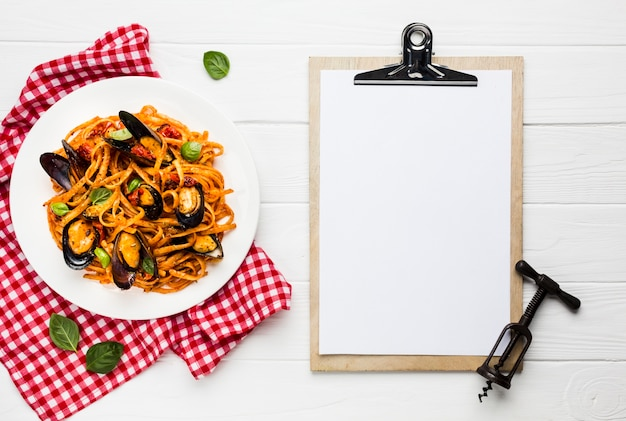 Flat-lay plate of mussels pasta with clipboard