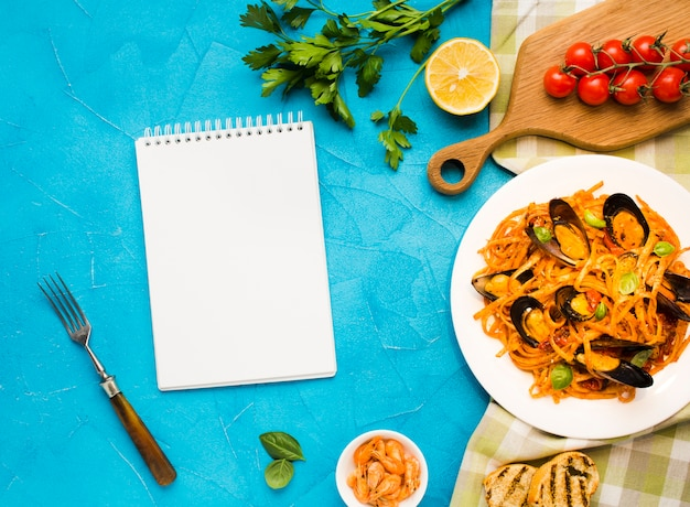Flat-lay plate of mussels pasta with notebook